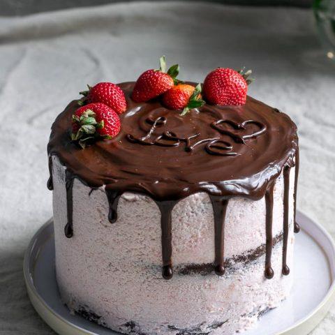 Chocolate cake with vegan aquafaba strawberry Italian meringue buttercream and a chocolate drip