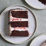 Three slices of three layer chocolate cake with vegan aquafaba strawberry Italian meringue buttercream and a chocolate drip