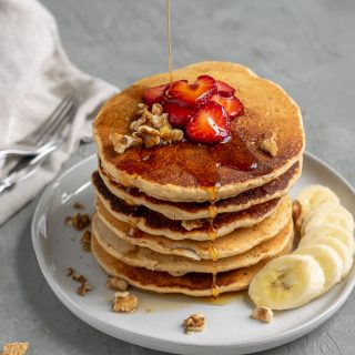 A stack of whole grain cornmeal vegan pancake mix, cooked and served with sliced strawberries, chopped walnuts, sliced banana, and a drizzle of maple syrup
