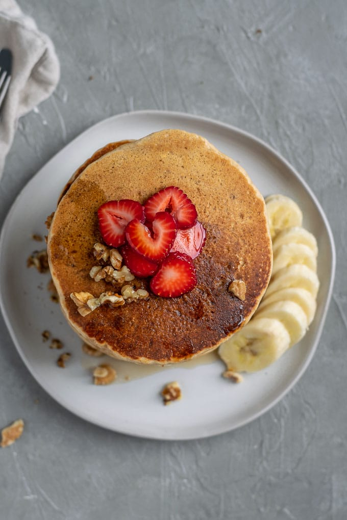 overhead view of a stack of make ahead whole grain cornmeal vegan pancakes topped with strawberry, additional walnuts and served with banana