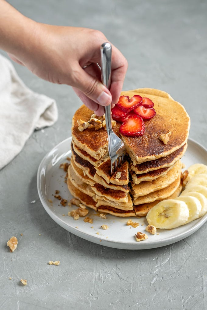 Digging a fork into whole grain cornmeal vegan pancakes cooked and stacked 6 tall