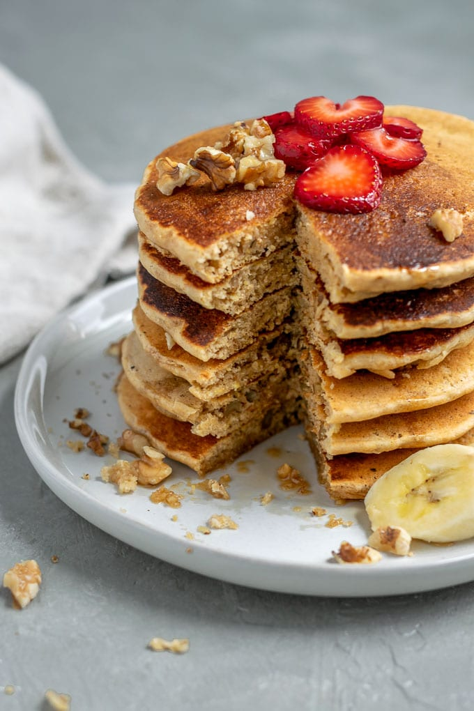 Make ahead whole grain cornmeal vegan pancake mix cooked and stacked 6 tall with a wedge cut open for a bite