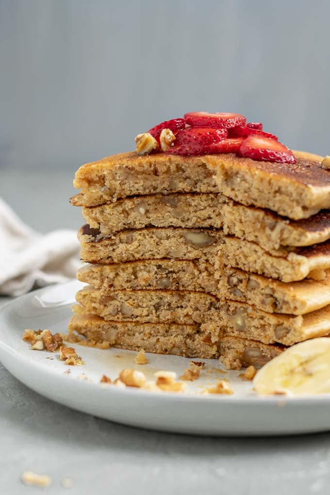 Make ahead whole grain cornmeal vegan pancake mix cooked and stacked 6 tall and sliced open to show the fluffy texture and chopped walnuts
