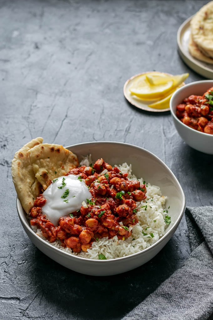 Restaurant style chana masala served with basmati rice, garlic naan, and lemon wedges