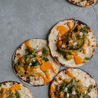 Paps con rajas tacos (potato with roasted poblano tacos) with a drizzle of creamy Mexican chipotle sauce