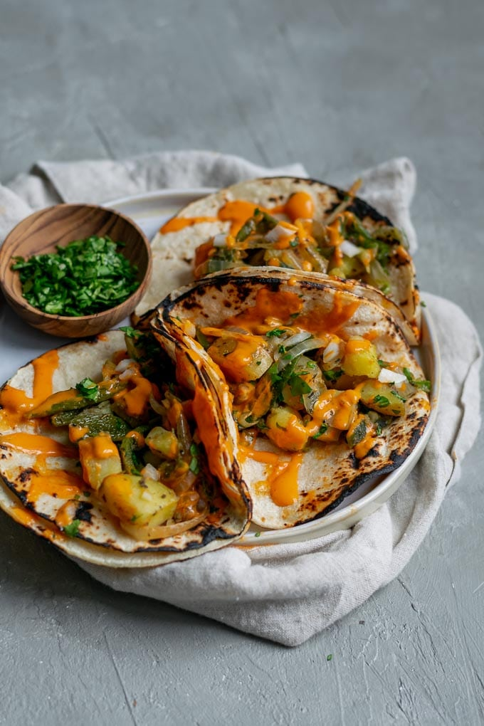 Paps rajas tacos (potato and roasted poblano tacos) with a drizzle of creamy Mexican chipotle sauce