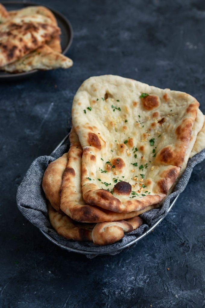 vegan homemade restaurant style naan, made into garlic naan and stacked in a bread basket, one piece in the background torn to serve