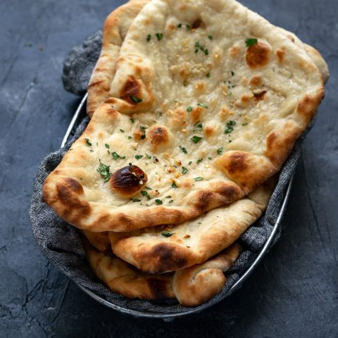 vegan homemade restaurant style naan, made into garlic naan and stacked in a bread basket