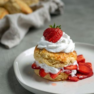 vegan strawberry shortcake with brandy soaked strawberries and vanilla bean whipped cream topped with a strawberry and extra shortbread biscuits in background