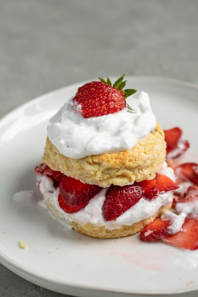 Close up of vegan strawberry shortcake with brandy soaked strawberries and vanilla bean whipped cream topped with a strawberry. A little messy with strawberries spilling out of the biscuit.