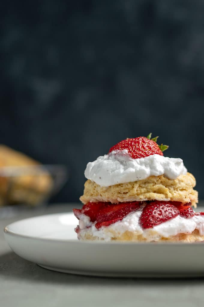 vegan strawberry shortcake with brandy soaked strawberries and vanilla bean whipped cream topped with a strawberry straight on close up shot. Extra biscuits in background.