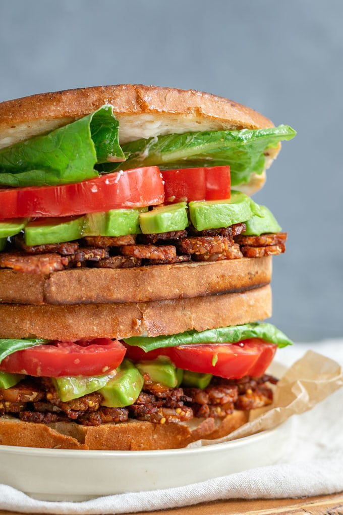 vegan tempeh bacon, lettuce, tomato, and avocado sandwiches closeup