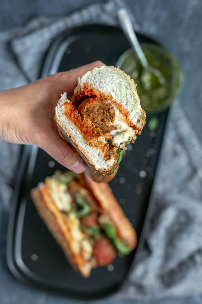 Vegan chickpea meatball subs with homemade mozzarella, pesto, and caramelized onions. View of the cut sandwich.