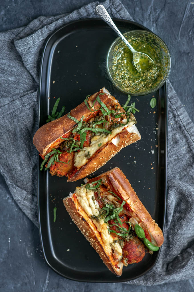 Vegan chickpea meatball subs with homemade mozzarella, pesto, and caramelized onions