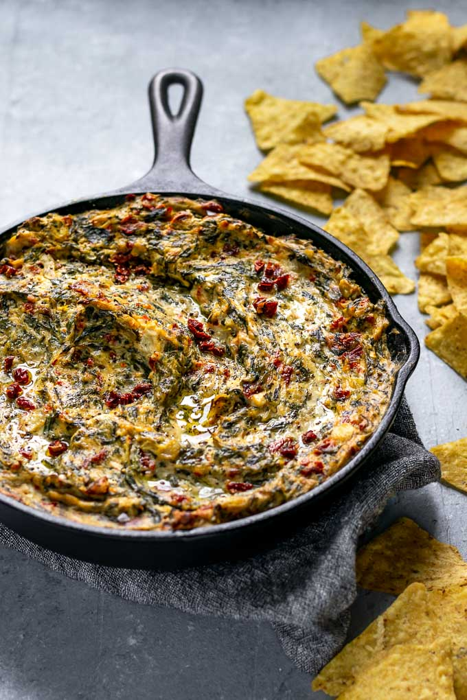 the best vegan spinach artichoke dip served with tortilla chips
