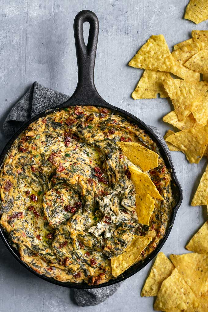 the best vegan spinach artichoke dip with tortilla chips in the skillet