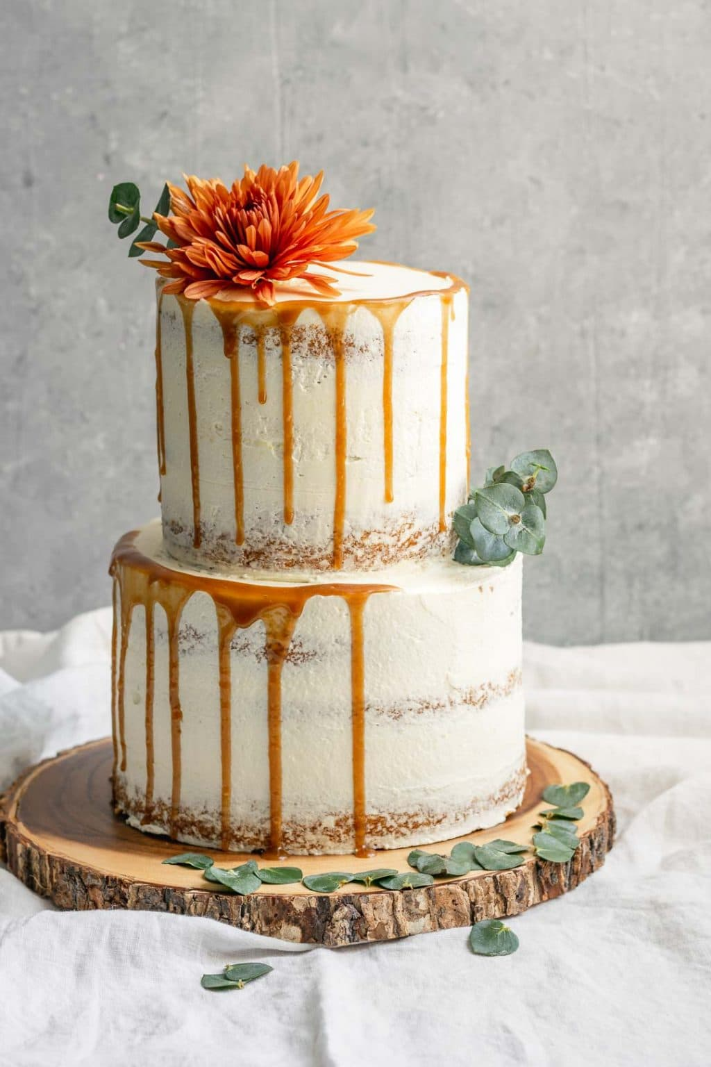 A 2-tier easy vegan vanilla cake decorated with flowers and a salted caramel drip