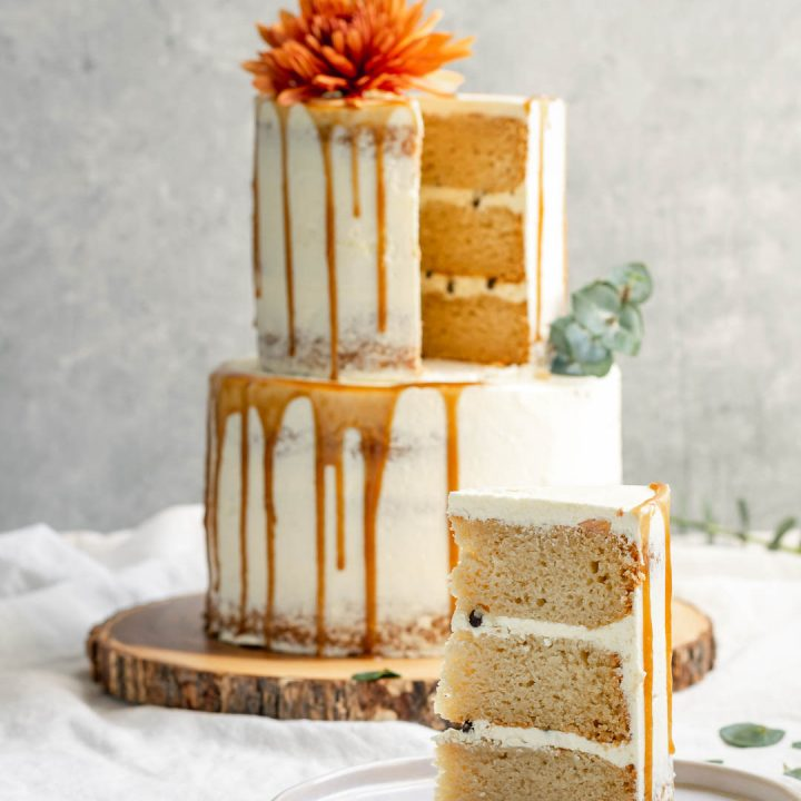 A 2-tier easy vegan vanilla cake decorated with flowers and a salted caramel drip with one slice cut out of it to reveal a 3 layer cake with chocolate chips in the buttercream filling