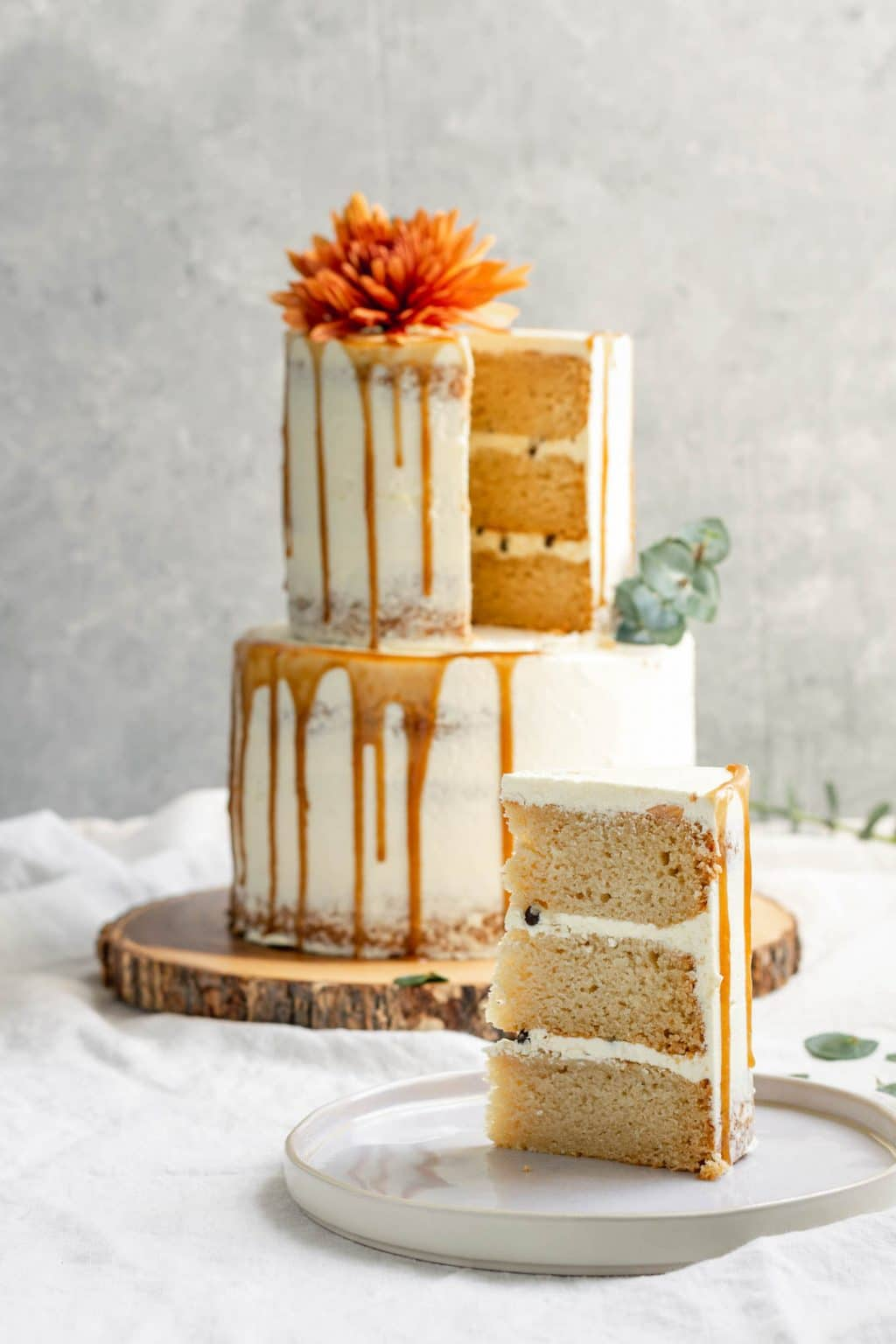 A 2 Tier Easy Vegan Vanilla Cake Decorated With Flowers And Salted Caramel Drip