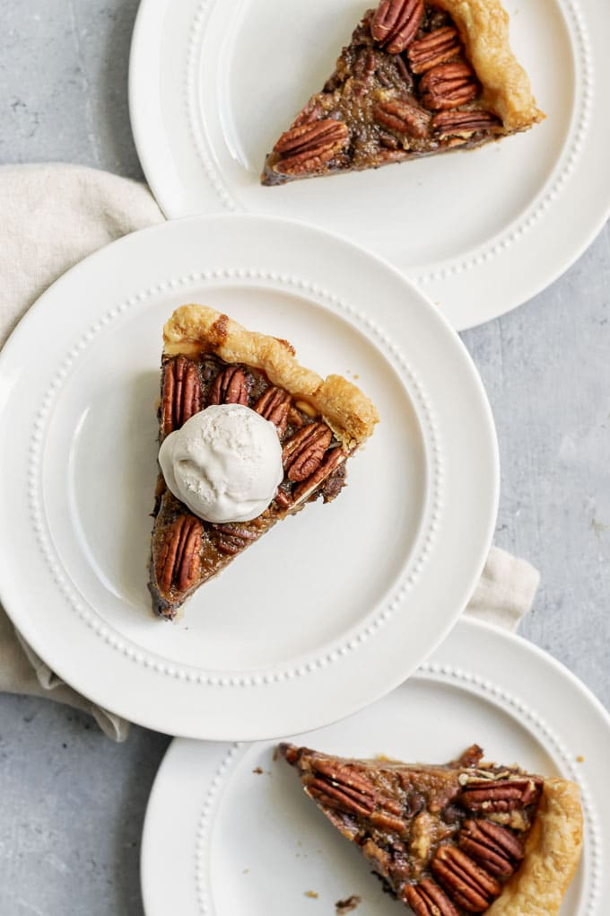 Three slices of vegan chocolate bourbon pecan pie with a scoop of vanilla ice cream
