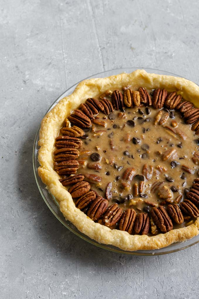 filled pie crust decorated with pecan halves before baking