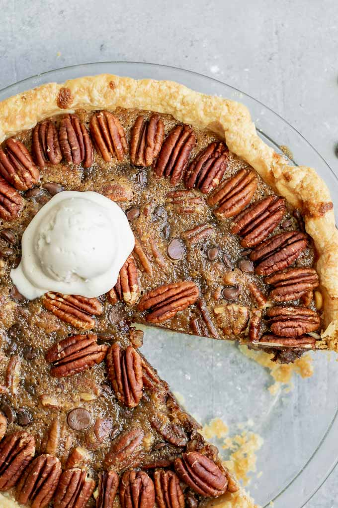 close up of a vegan chocolate bourbon pecan pie with a scoop of non-dairy vanilla ice cream and a slice taken out