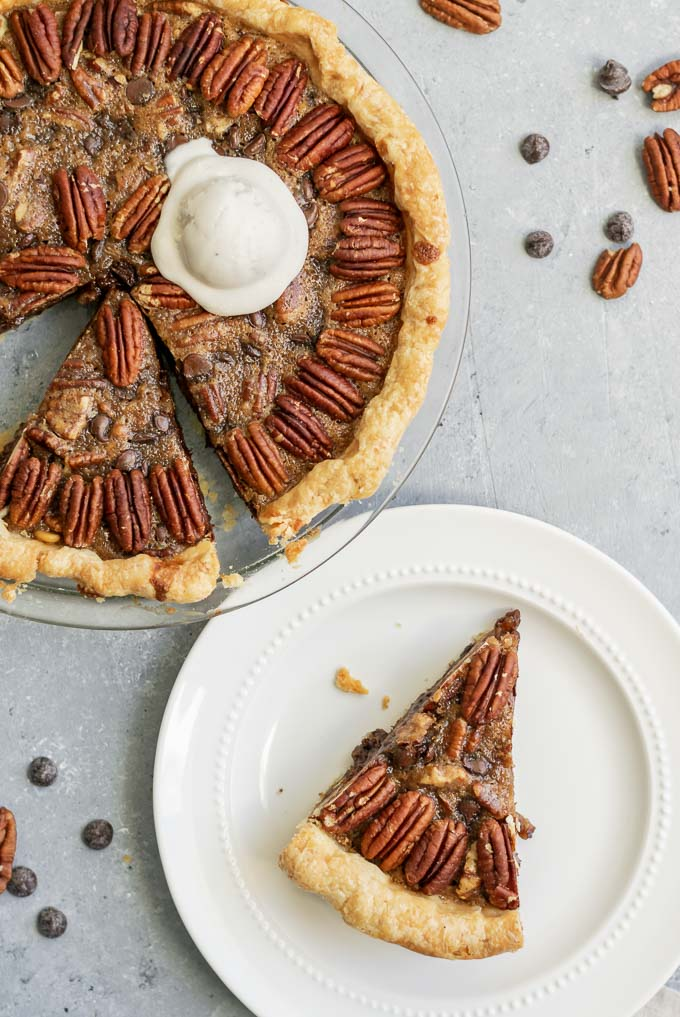 vegan chocolate bourbon pecan pie with a scoop of ice cream and two slices cut out, one on a plate