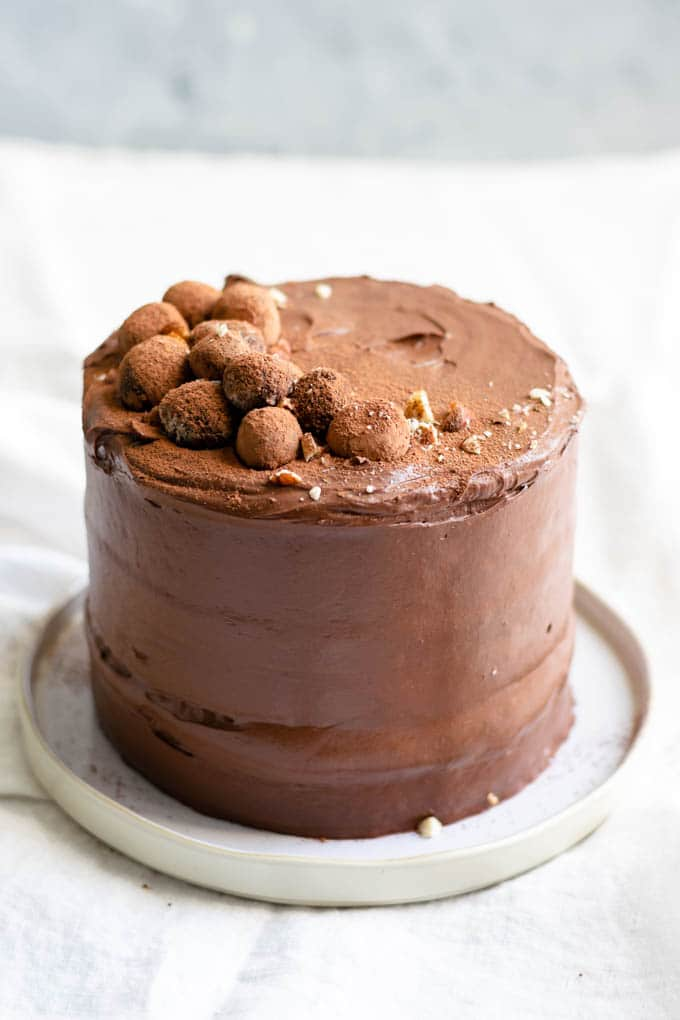 Vegan hazelnut cake frosted with a whipped chocolate ganache topped with chocolate hazelnut truffles and dusted with cocoa powder