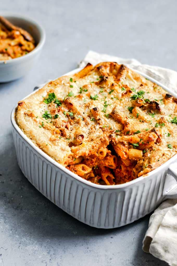 vegan baked ziti in a casserole dish with one serving in a bowl in the background