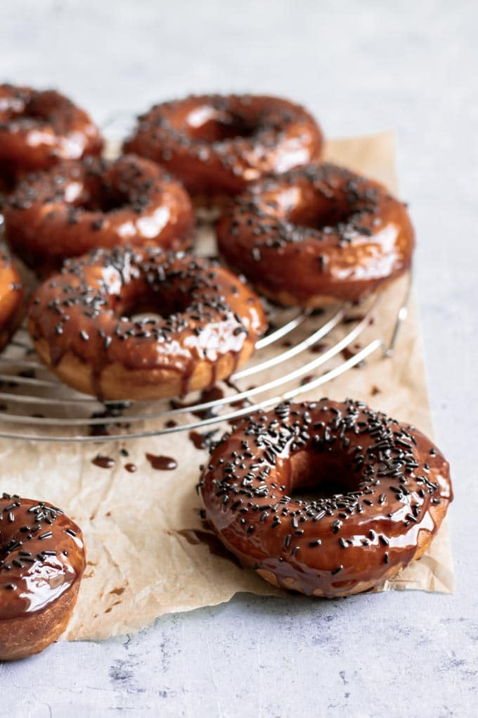 vegan chocolate glazed doughnuts with chocolate sprinkles, viewed from an angle