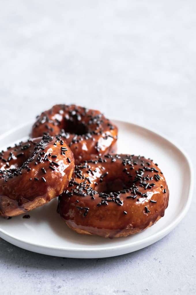 three vegan chocolate glazed doughnuts on a plate