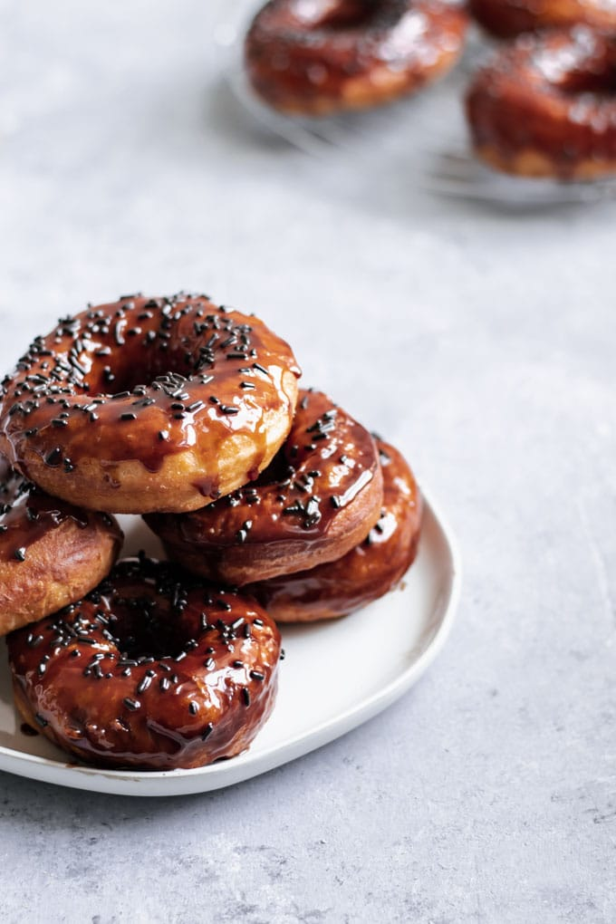 vegan chocolate glazed doughnuts stacked on a plate