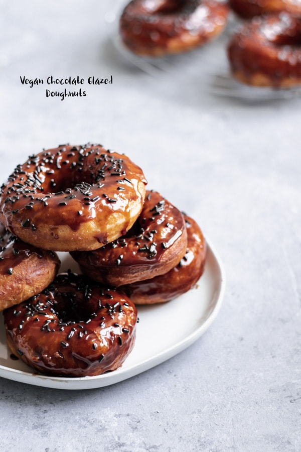 These delicious classic yeasted chocolate glazed doughnuts are made vegan and covered with sprinkles and rival those in your favorite traditional doughnut shops! | thecuriouschickpea.com #vegan #vegandoughnuts #vegandonuts #donuts #doughnuts #chocolate #veganbreakfast #vegandessert