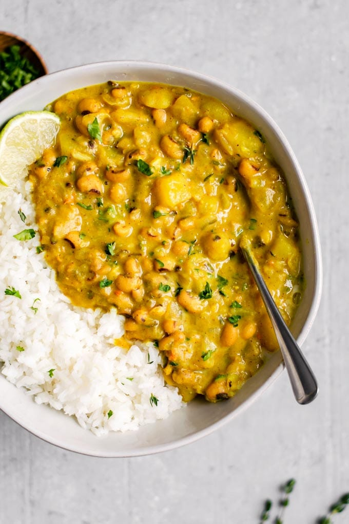Jamaican black-eyed pea curry served with lime wedges and rice