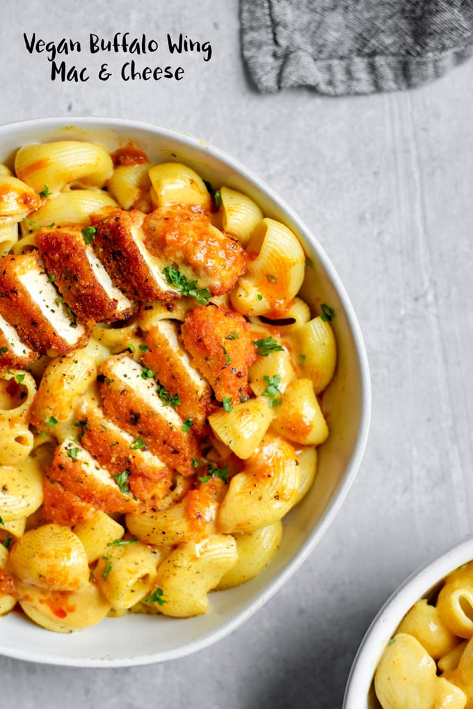 Easy, creamy coconut milk mac and cheese is topped with cripsy baked buffalo tofu wings for the most epic and mouth-watering meal! | thecuriouschickpea.com #vegan #vegancheese #buffalowings #tofu #veganpasta #macandcheese