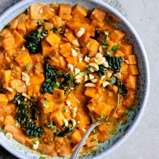A large bowlful of West African curry sweet potato, kale, and peanut stew