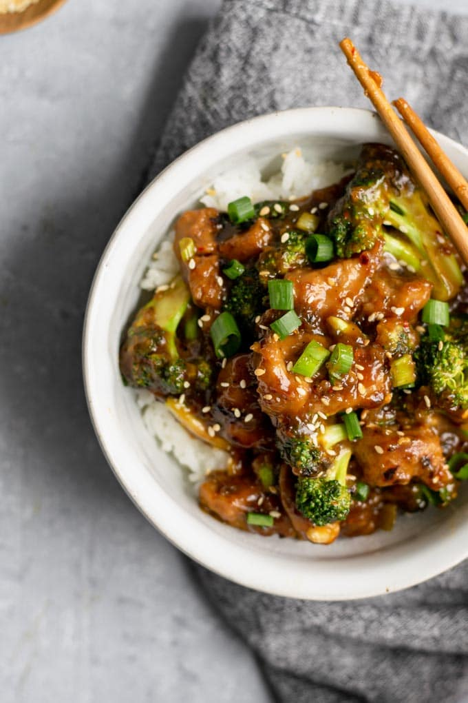 crispy orange seitan and broccoli with jasmine rice, with sticky chopsticks resting on bowl