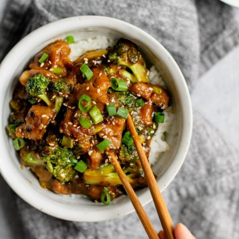 crispy orange seitan and broccoli with jasmine rice, grabbing a piece of seitan with chopsticks