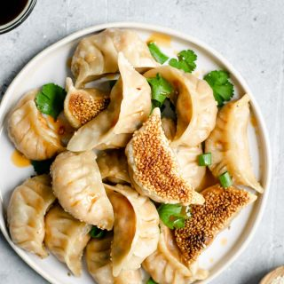 Gochujang tofu dumplings with a chili oil drizzle and cilantro to garnish