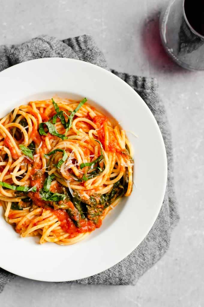 spaghetti with classic homemade marinara with spinach and a glass of red wine