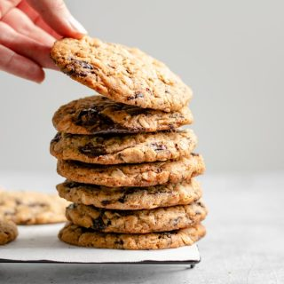 grabbing a cookie off the top of a stack of vegan peanut butter oatmeal chocolate chip cookies