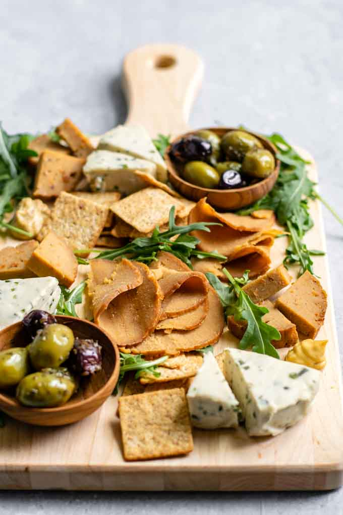 homemade seitan deli meat slices and wedges on a cheese board with crackers, vegan cheeses, mustard, olives, and arugula for garnish
