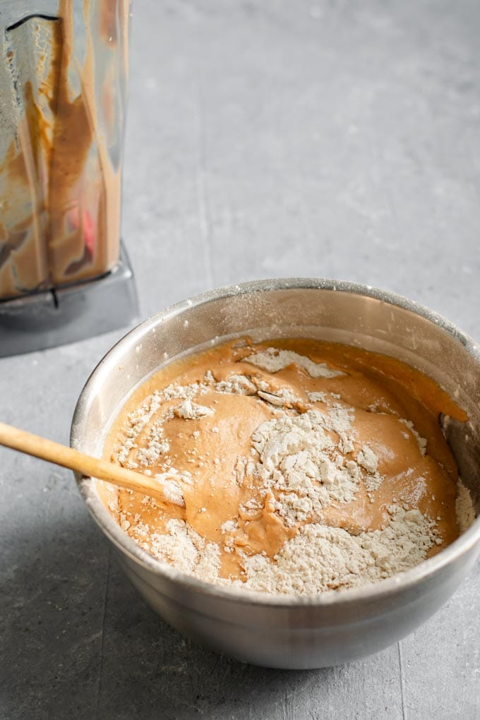 Mixing in the wet and dry ingredients with a wooden spoon