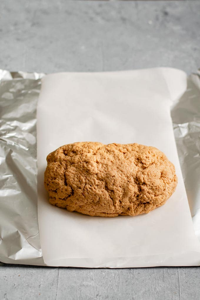 seitan dough sitting on prepared parchment paper lined aluminum foil. The seitan dough has been kneaded and shaped into a log.