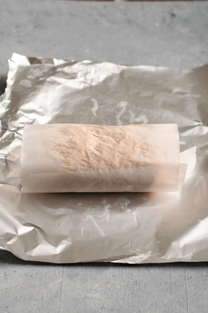 Seitan dough wrapped in the parchement paper and ready to be wrapped in the foil