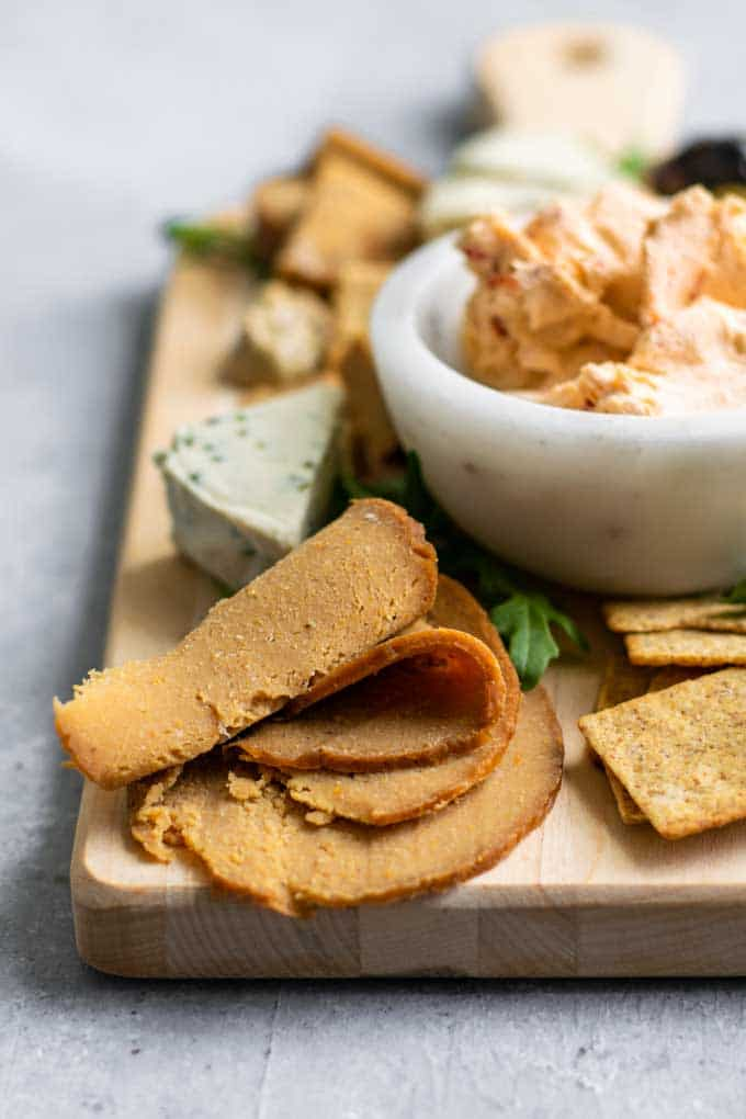 homemade seitan deli meat slices on a cheese board with crackers, vegan cheeses, mustard, olives, and arugula for garnish