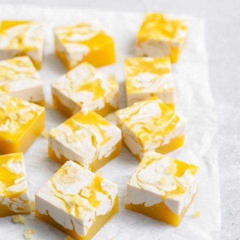 vegan mango jalapeño jello shots with a ginger cream swirl, garnished with minced crystallized ginger