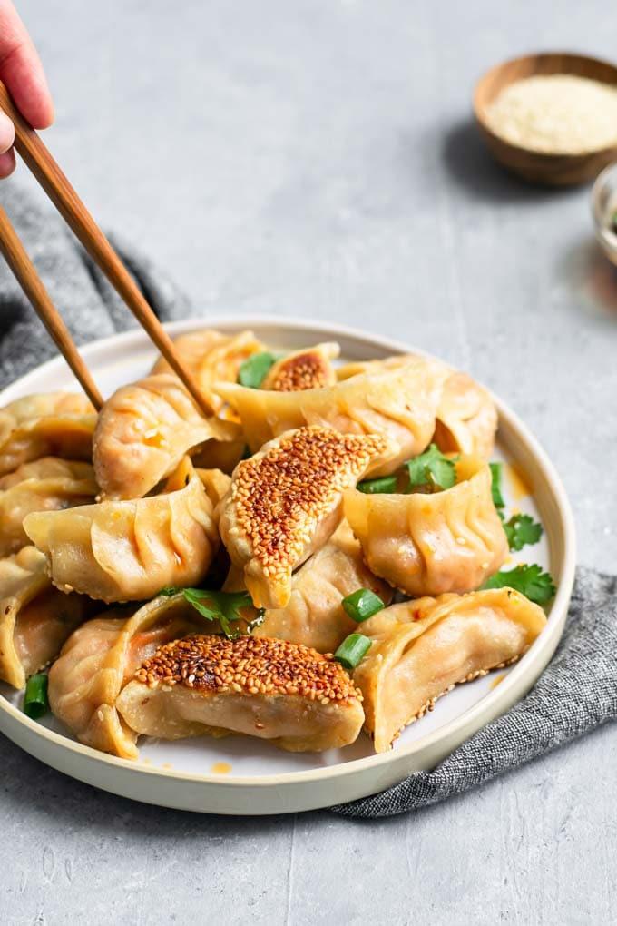 picking up a dumpling with chopsticks