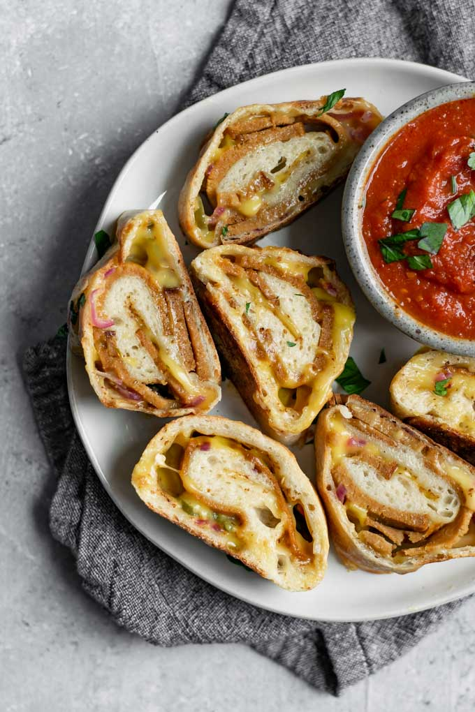 vegan stromboli, sliced and served on a plate with marinara for dipping