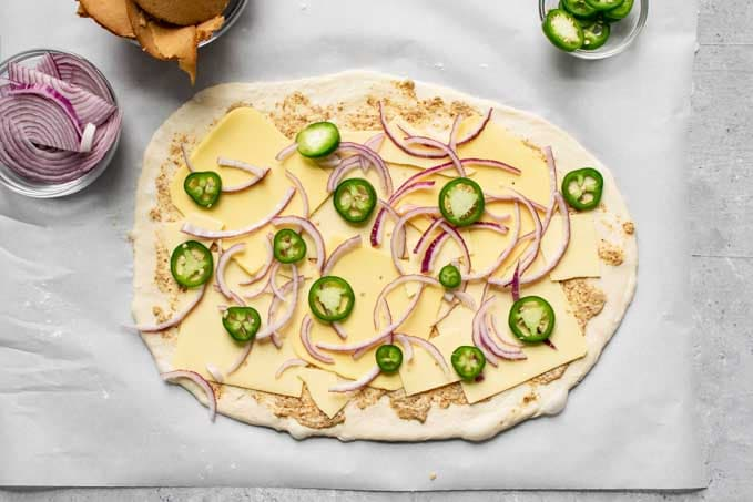 pizza dough topped with mustard, vegan cheese slices, jalapeño and red onion for stromboli